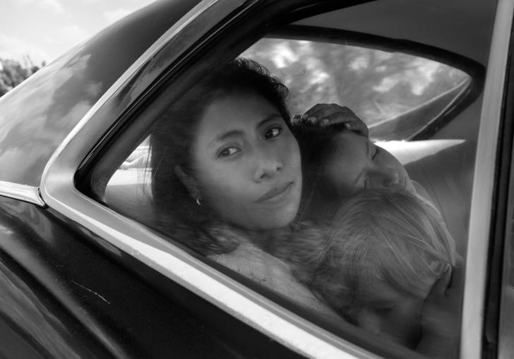 A woman hold a child in the back seat of a car and looks longingly out of the window. The image is a still from the film Roma