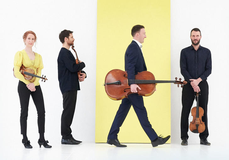 Heath String Quartet on white and yellow background holding instruments