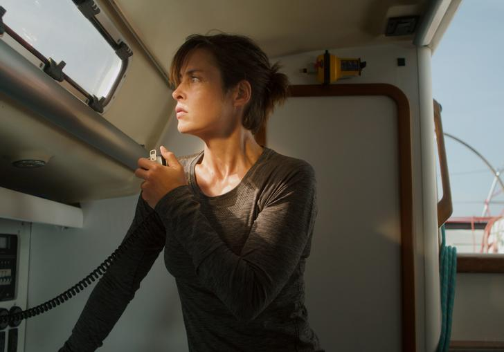 A woman in a grey top on the radio of her boat.