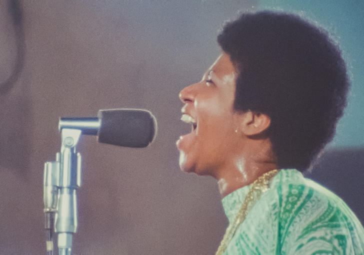Aretha Franklin singing in green