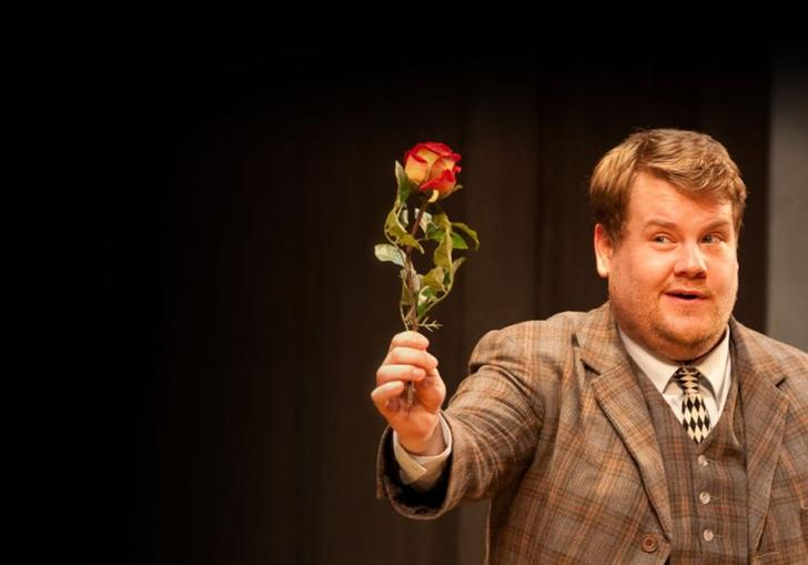 James Corden in a tweed three-piece holding a single flower