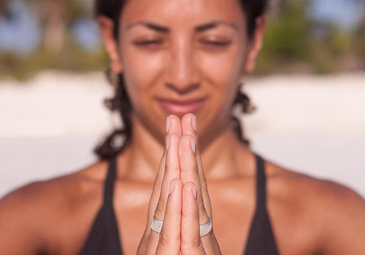A person pushing their hands together in a yoga pose