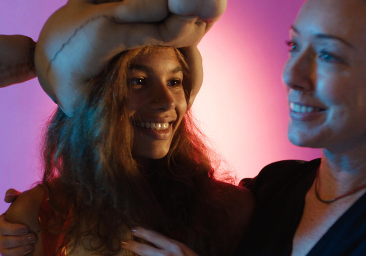 Lead actress Helena Howard in an animal hat, smiling in front of soft pink lighting.