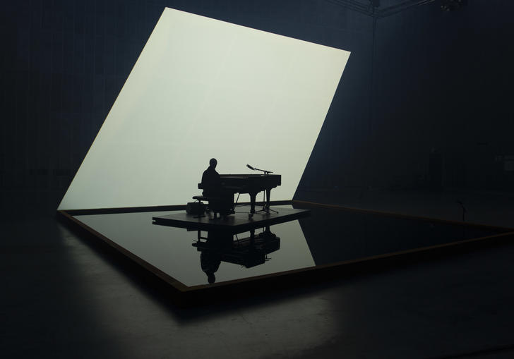 Nik Bartsch playing solo piano on a pool of water, with a lit white backdrop