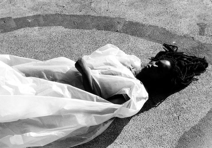 Moor Mother lying on a concrete floor