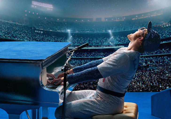 Taron Egerton as Elton John singing at a piano