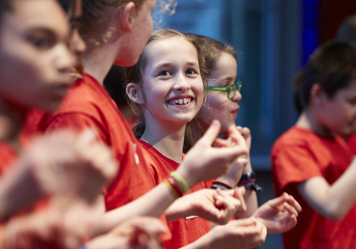 Members of the LSO Discovery Junior Choir sing in red t-shirts