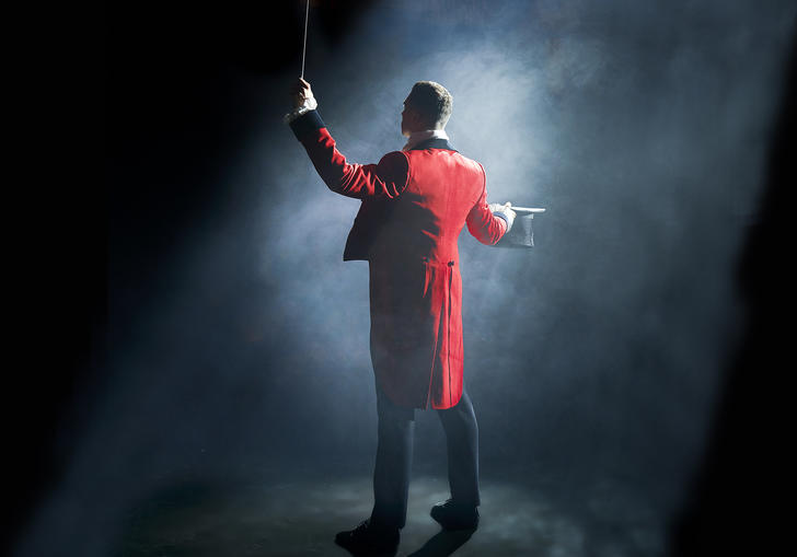 A circus ringmaster standing in a spotlight