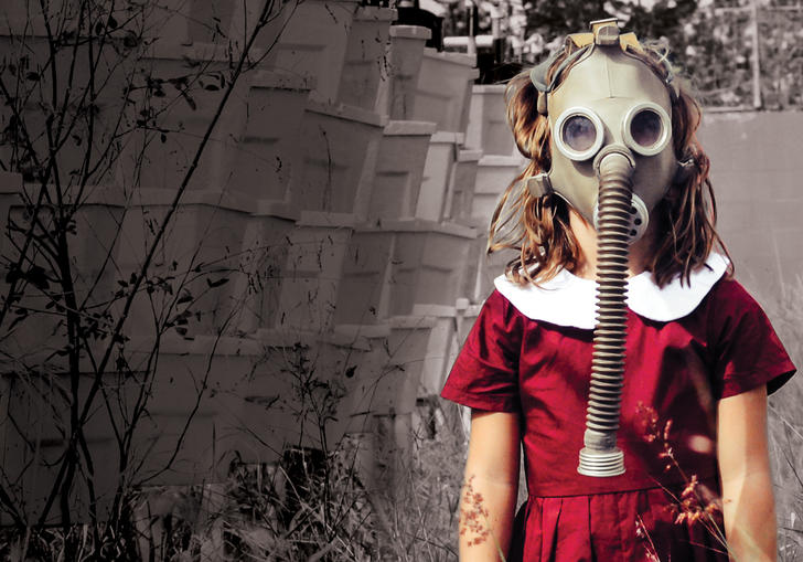 Young girl with gas mask standing in long grass