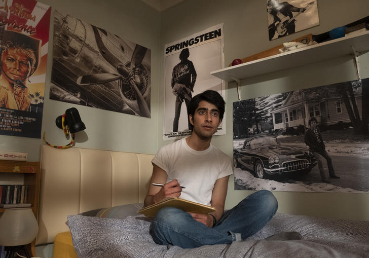 Viveik Kalra sitting on his bed surrounded by Bruce Springsteen posters