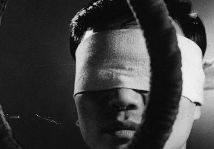 blindfolded man standing behind a noose