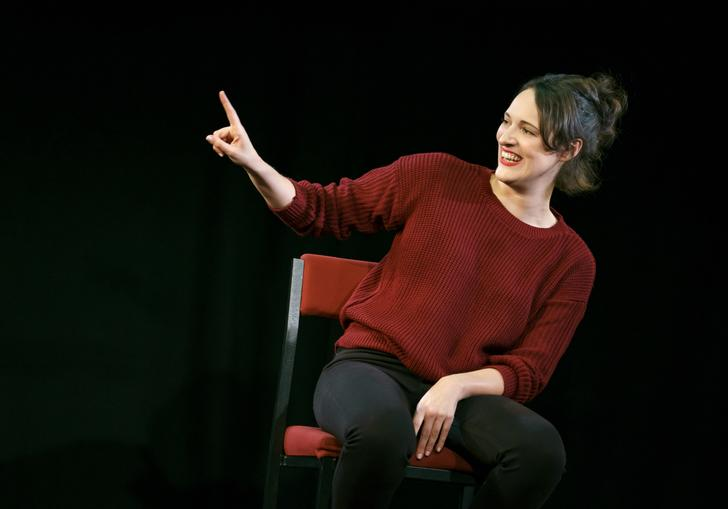 Phoebe Waller-Bridge sitting on a chair in a dark space with her arm and finger pointing up