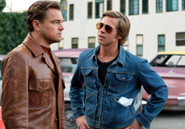A teary eyed Leo Dicaprio talking to Brad Pitt in the street