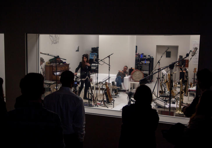 A group of musicians standing in a recording studio being watched by the producers in the next room