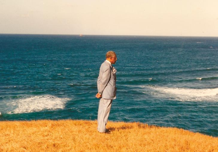 Aimé Césaire looks out to sea in a pale suit, with bright yellow grass beneath him
