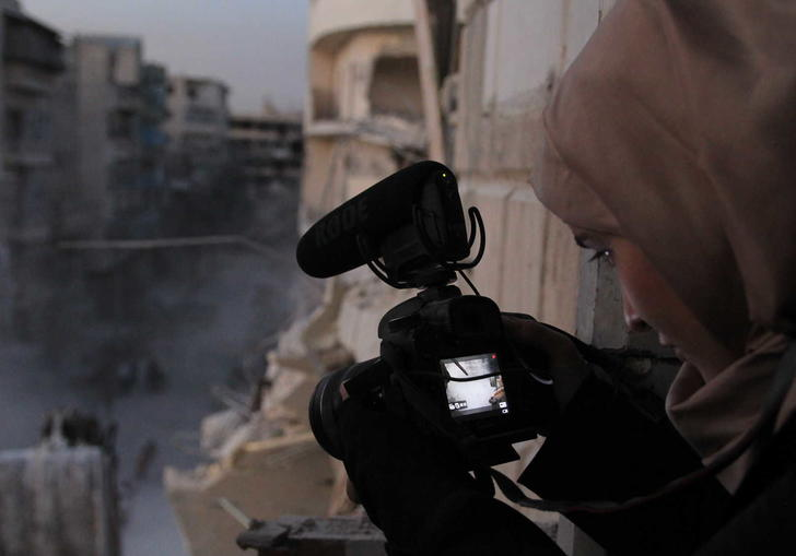 Waad with a camera pointing down to the street which is covered in dust and rubble