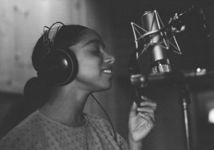 Lianne La Havas singing into a microphone
