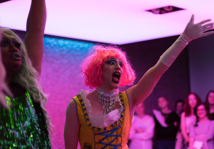 A Drag Queen with a pink wig singing