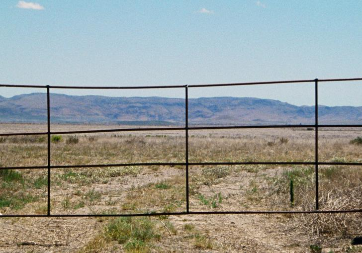 a fence set against a desert like backdrop with mountains and blue sky