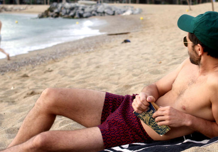 A man reclines on a beach in dark pink shorts and a teal cap, holding a book and looking at another man by the sea