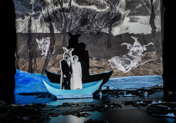 A figure that is half-man, half-kangaroo is standing in a boat with Fleur Elise Nobel's unnamed character. They look like figures in a pop-up book, against a paper painted backdrop and vivid blue colour in the water. Their shadows are prevalent against the paper backdrop.