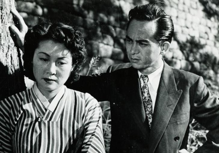 A woman standing infront of a cliff face with a man leaning behind her and looking at her