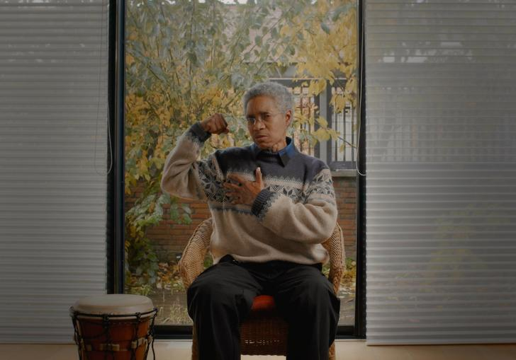Glenn Copeland flexes a bicep in a grey and cream woolly jumper, in front of a window, next to a drum