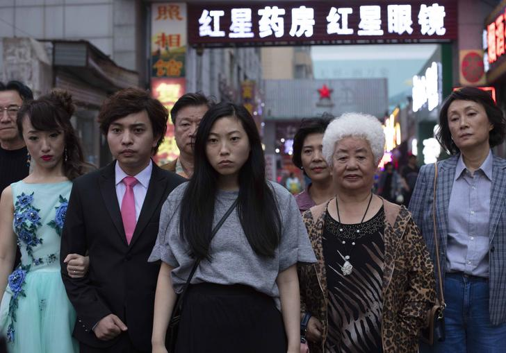 Awkwafina starring in The Farewell standing with her family around her