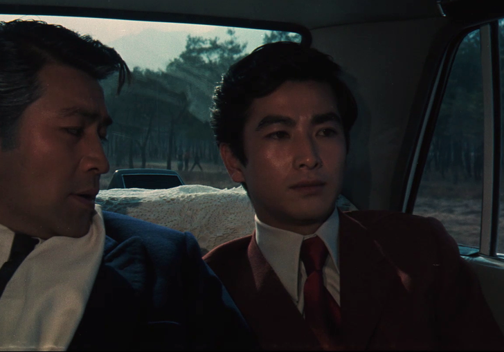 two men sitting in a dark car together