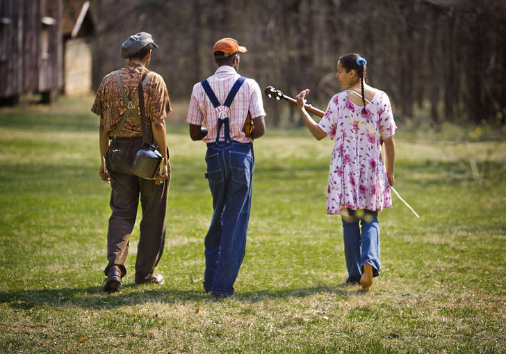 the Carolina Chocolate Drops trio from behind, as they walk with their instruments in a field