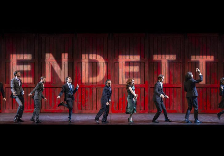 Ten people stand in various poses in front of a red wall which spells out 'vendetta'
