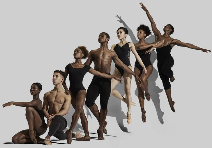 seven dancers are in a line in serveal balletic poses. The positions range from low to the ground, to the dancer at the back of the line in a jump.