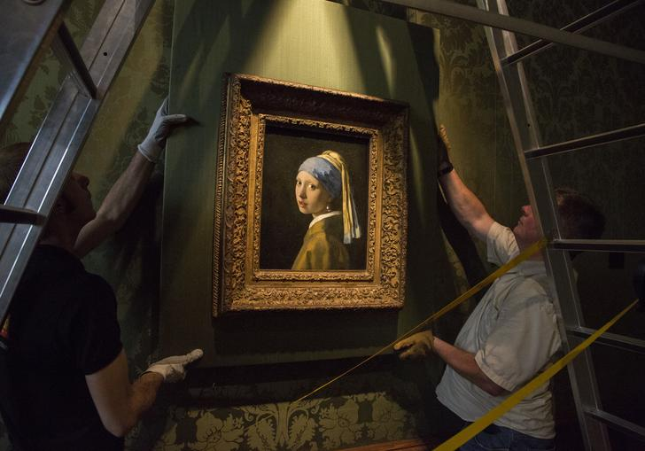 two people putting up the girl with the pearl earring painting