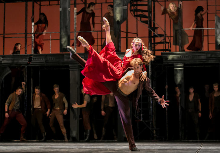 dancer is red dress is held up by a male dancer with his shirt open