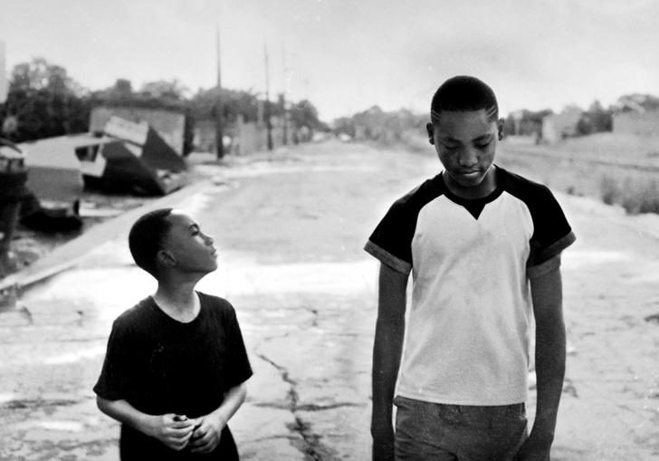 two boys walking down the street in black and white