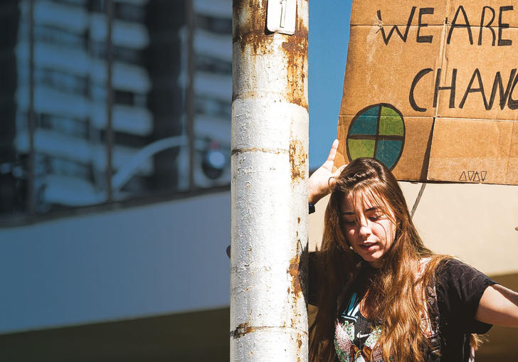 Image of a young woman holding banner at a protest