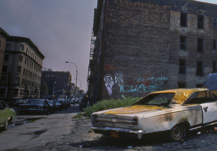Image of burnt-out car in run down city with graffiti on walls