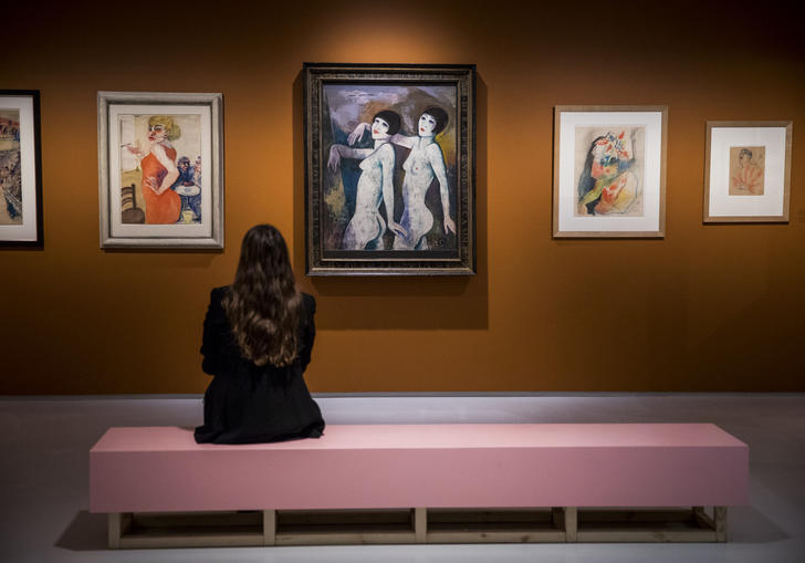 Woman looking at a painting of two figures
