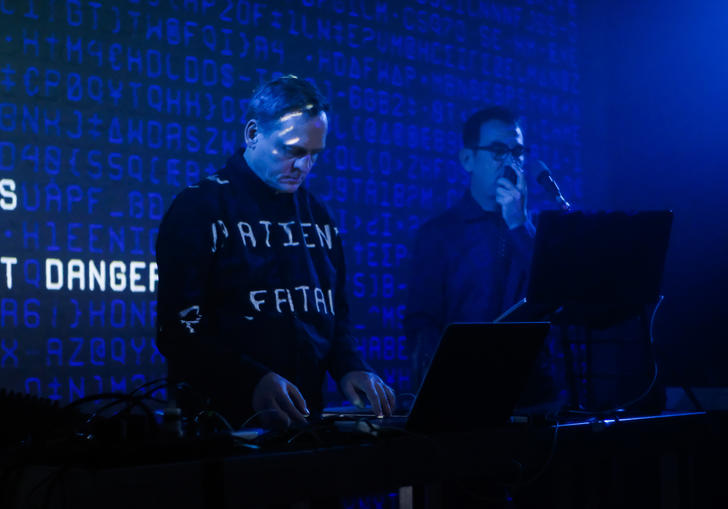 Alva Noto and Anne-James Chaton performing with a laptop and microphone. Words are projected behind them and onto their clothes
