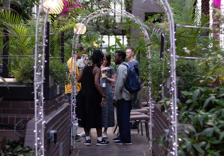 Group of people talking in the barbican conservatory
