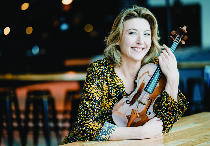Candida Thompson sitting at table holding violin