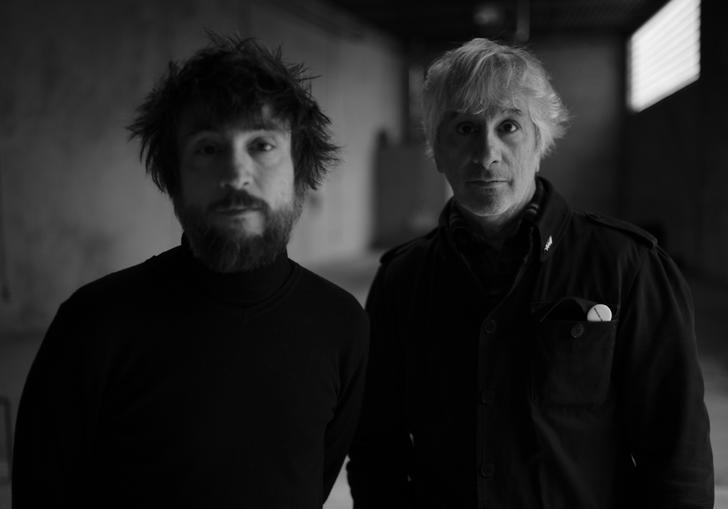 A black and white photo of Lee Ranaldo and Raul Refree in an empty concrete room, wearing black shirts