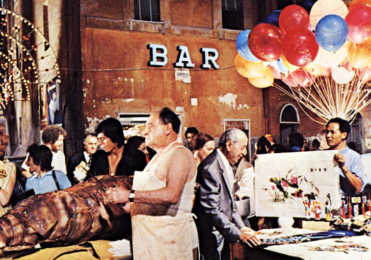a market in a Rome square, there are balloons, meat and tables with people milling around