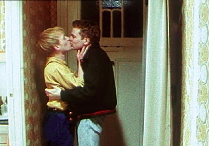 Two men kiss in a 1980s hallway in East Germany, in Wieland Speck's Westler