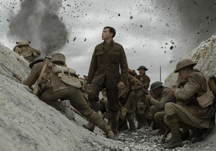 George MacKay stands in the trench surrounded by explosions and other men