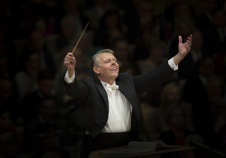 Mariss Jansons with raised arms conducting
