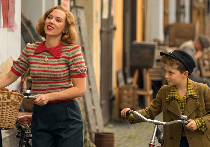 scarlett Johanssen and little Jojo walking down the street pushing bicycles