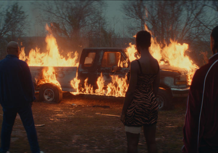 people standing in front of a burning car