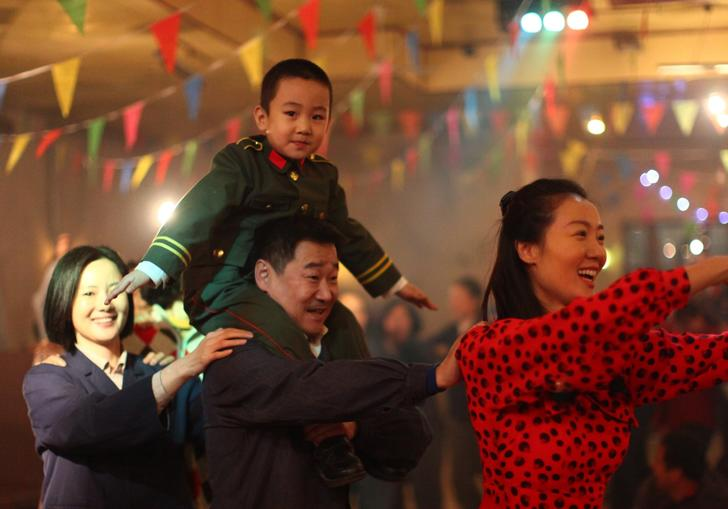 little boy on his father's shoulders dancing