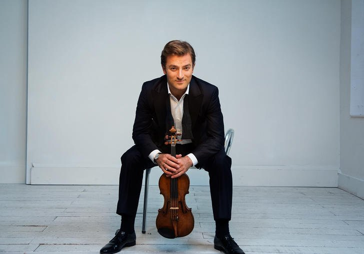 Renaud sitting on a chair in a white room with a cheeky grin on his face, clutching his violin